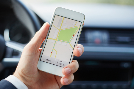 O homem sentado no carro e prende o telefone móvel branco com mapa de navegação GPS