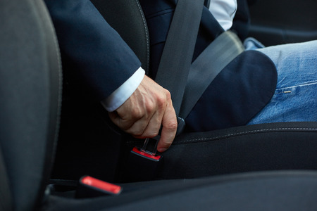 Driver sits in the car and fastens his seat belt
