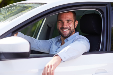 Portrait of an handsome man driving his car