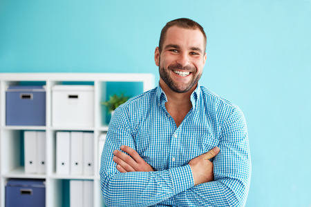 Young businessman sitting on desk with crossed arms in office