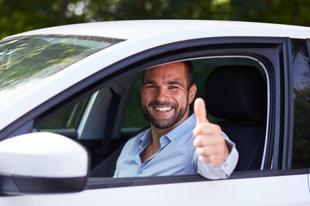 Man driving his car and makes gesture with thumb up Фото со стока