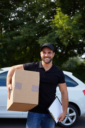 removal van: Young delivery man holding a paper box and folder