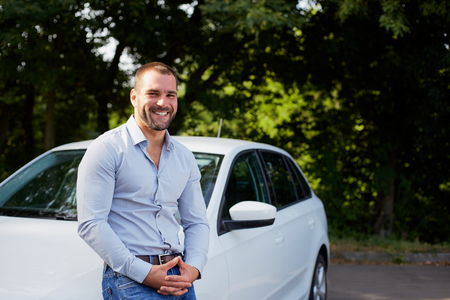 car salesperson: Handsome man on the background of car