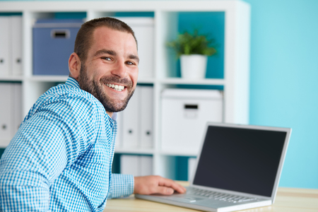 Happy businessman working in modern office on computer Stockfoto