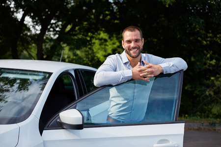 Handsome man standing and leaning on car door
