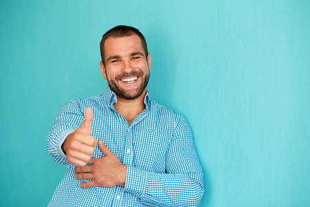 person: Happy man with thumb up on a turquoise background Stock Photo