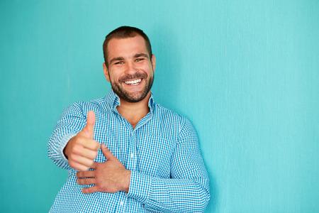 Hombre feliz con el pulgar hacia arriba sobre un fondo azul turquesa