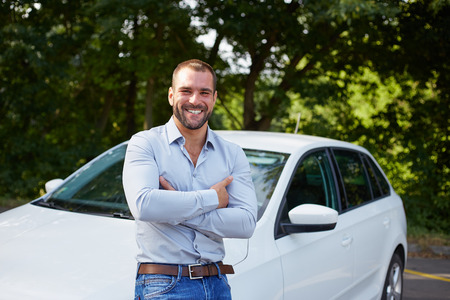 car salesperson: Handsome man standing in front of car