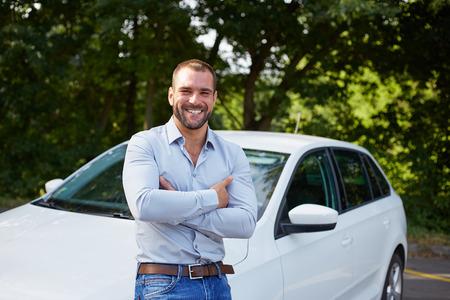 automobile dealer: Handsome man standing in front of car