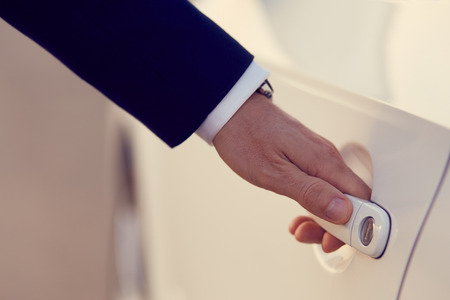 abrir puertas: Mano de hombre de negocios en traje formal de abrir una puerta de coche, tonificado
