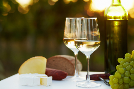 wine glasses: Two glasses of white wine with food at sunset Stock Photo