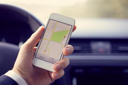 Homem sentado no carro e segurando o telefone celular branco com mapa GPS de navegação, tonificado