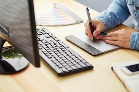 grafiken: Grafikdesigner auf einer digitalen Tablette arbeitet im Büro