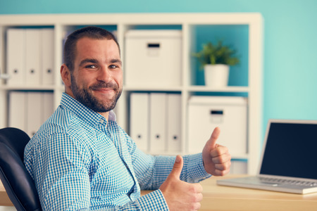Businessman working on laptop and making the ok gesture, toned