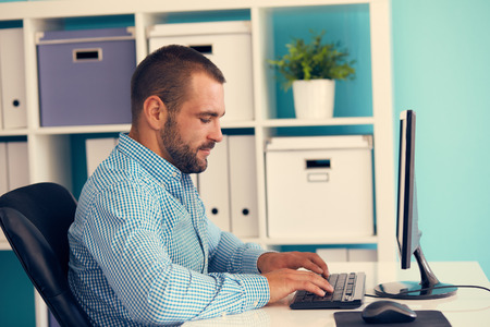 white person: Young businessman working in modern office on computer, toned Stock Photo