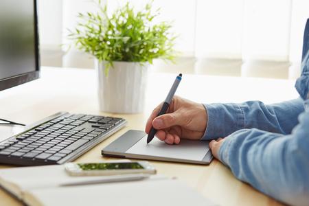 Diseñador gráfico trabajando en una tableta digital en el cargo