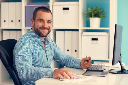 trabajando en casa: Feliz dise�ador gr�fico trabaja en la tablilla digital, tonificado Foto de archivo