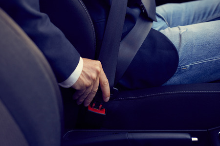 fastens: Driver sits in the car and fastens his seat belt