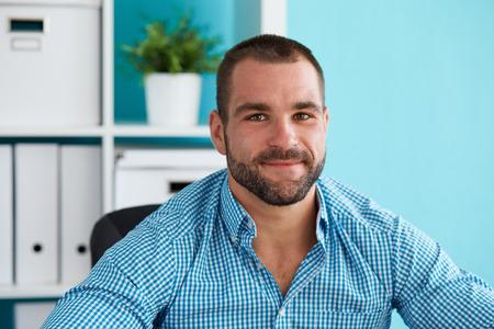Jonge man zit achter een bureau in moderne kantoor