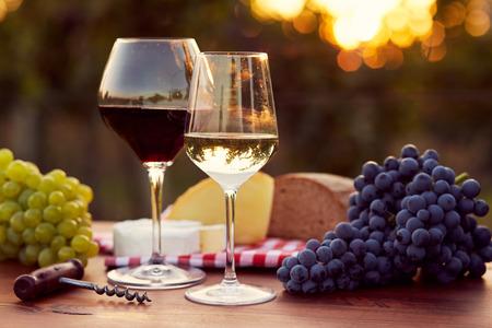 pan y vino: Dos vasos de vino blanco y tinto con la comida al atardecer, tonificado