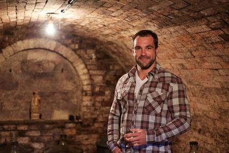 mature man: Man tasting a glass of white wine in wine cellar.