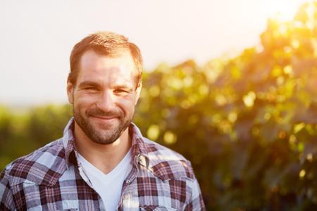 winemaker: Portrait of a young winemaker in vineyard, toned.