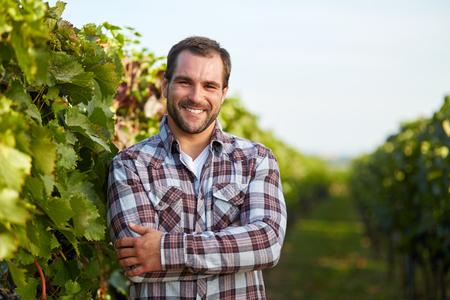 Jonge wijnmaker in de wijngaard met de armen gekruist