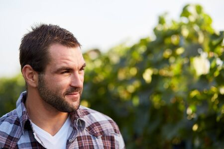 seasonal worker: Portrait of a young winemaker in vineyard Stock Photo