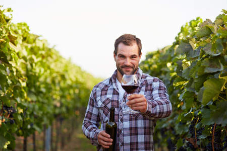 winemaker: Winemaker in vineyard with a glass of red wine and bottle