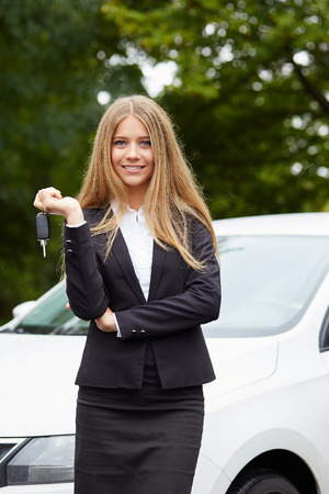 key: Young business woman with car key in hand Stock Photo