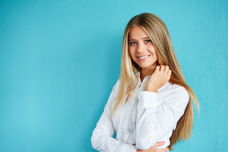 woman white shirt: Portrait of a beautiful young business woman standing against blue background Stock Photo