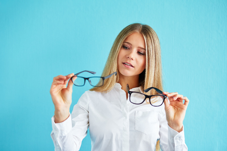 decides: Pensive businesswoman with glasses standing before blue background Stock Photo