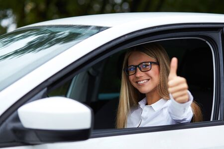 auto leasing: Woman driving his car and makes gesture with thumb up Stock Photo