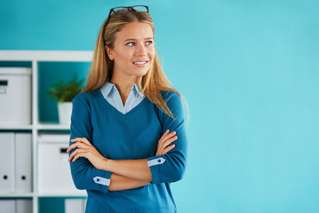 cross arms: Businesswoman standing in office with crossed arms and looking out the window