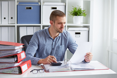 Pensive businessman calculates taxes at desk in office