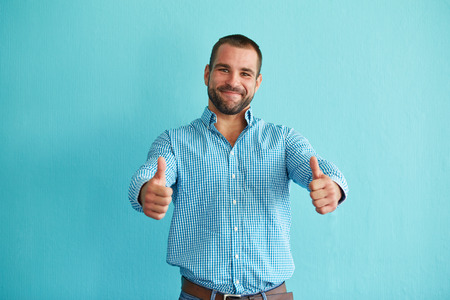 Happy man with thumbs up on a turquoise background