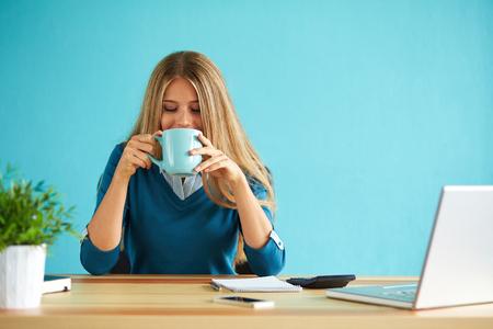 mujer tomando cafe: Joven beber café en la oficina Foto de archivo