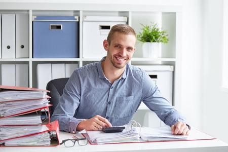 sonriente: hombre de negocios sonriente calcula los impuestos en el escritorio en la oficina