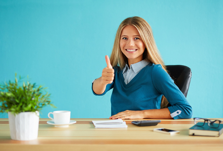 Happy business woman gesturing thumbs up in office Foto de archivo