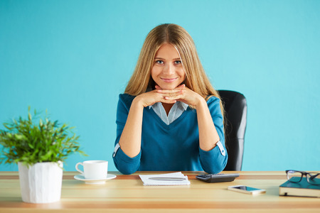 only women: Young woman sitting in office with her chin resting on her hands