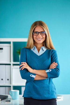 blue shirt: Young business woman standing in office with crossed arms