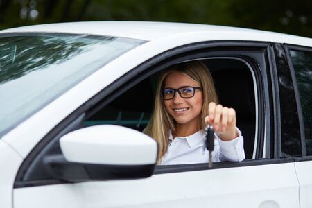 new driver: Happy woman Sitting in the car holding key from dealer in auto show or salon Stock Photo