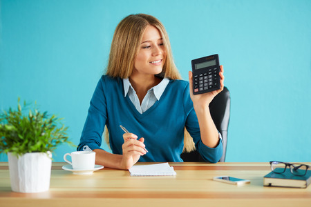 Smiling business woman showing calculator in office Stockfoto