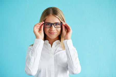 young women: Businesswoman in white shirt with glasses, standing over blue background. Stock Photo