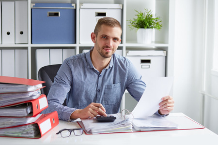 Young businessman calculates taxes at desk in office