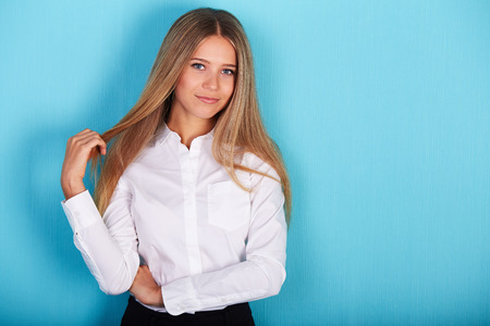 Portrait of a beautiful business woman standing against blue background Stock Photo