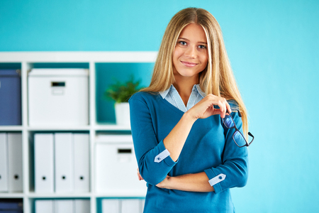 girl on a beautiful background: Young businesswoman with glasses standing in office Stock Photo