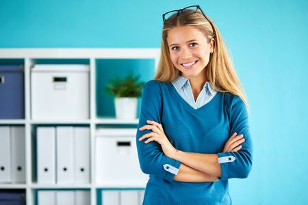cross arms: Smiling business woman standing in office with crossed arms