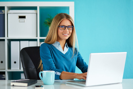 ejecutivo en oficina: Mujer de negocios joven que trabaja en la oficina moderna en el ordenador Foto de archivo