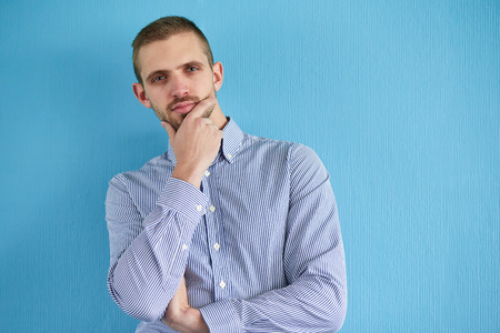 leaning against: Pensive man leaning against a blue wall Stock Photo